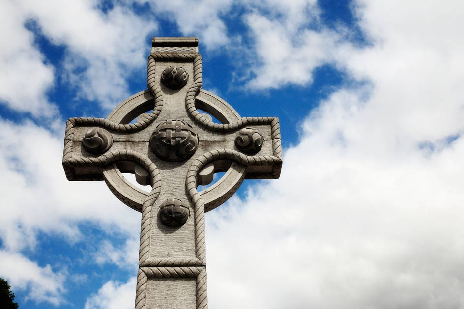 photo of stone cross, blue sky background